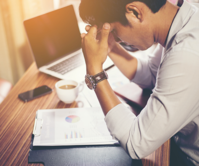 Stressed man looking at finances. Real Estate in Germantown, WI | House to Home Realty Team